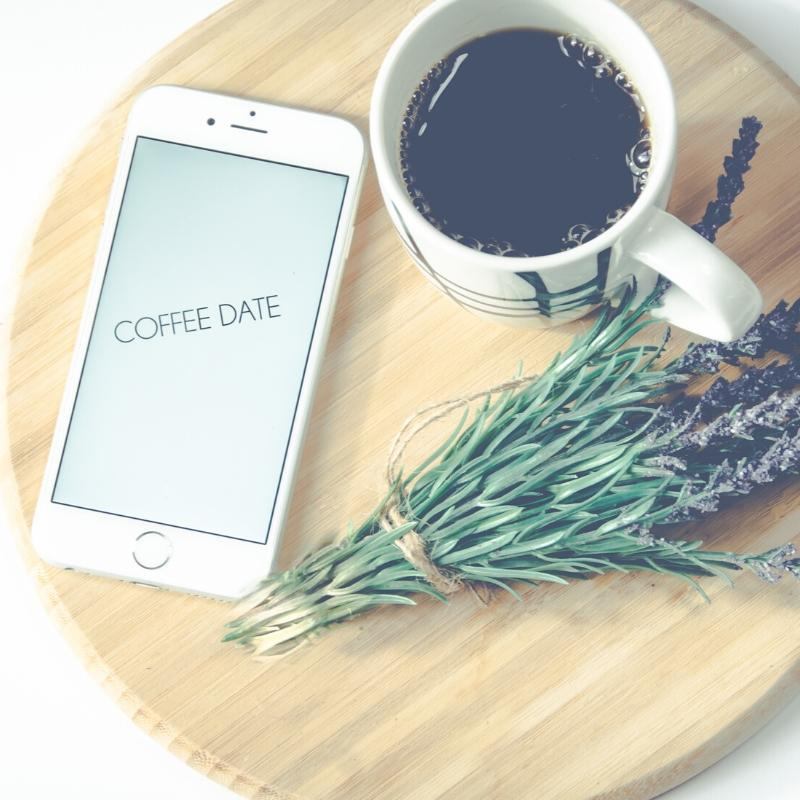 black iced coffee with iPhone and rosemary for decorations