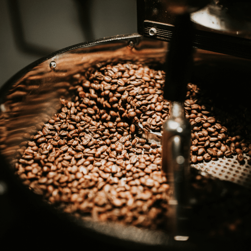 whole coffee beans being grinded in machine