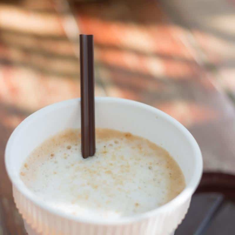 latte in a plastic cup with a brown straw