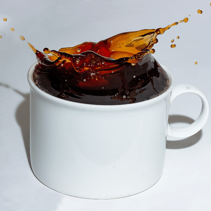 black coffee mid-splash after dropping in sugar cube
