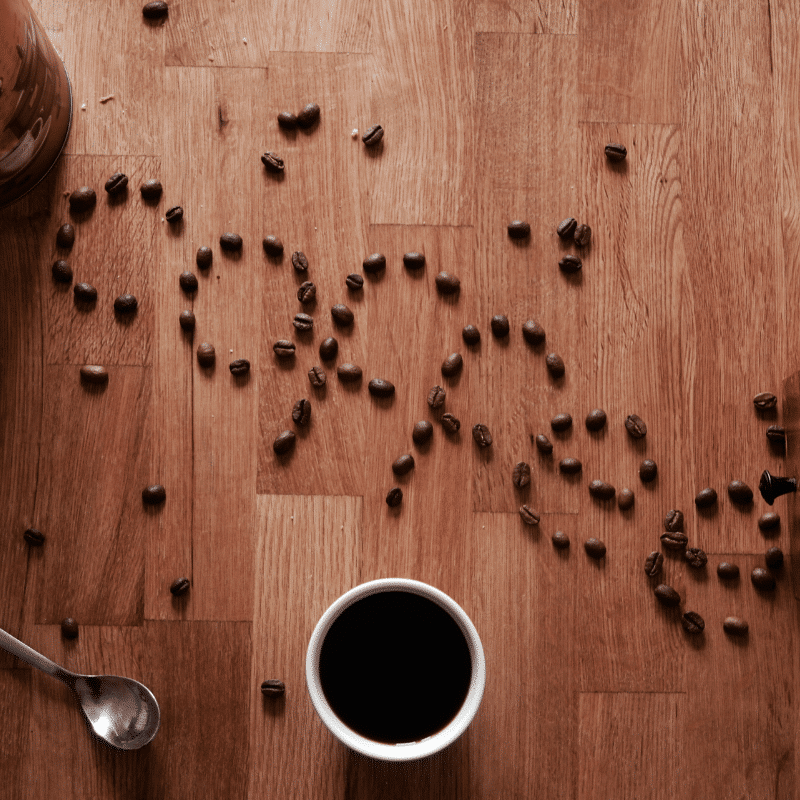 coffee beans sprinkled on floor with a cup of black coffee on the side.