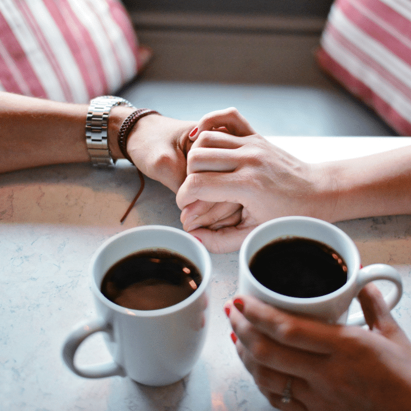 couple holding each others hand with black coffee in the other
