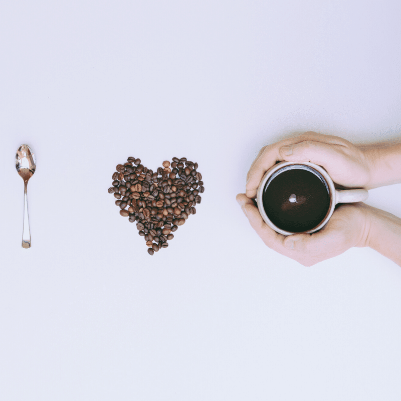 decorated black coffee with a love heart made from many black coffee beans, and a silver spoon to the left