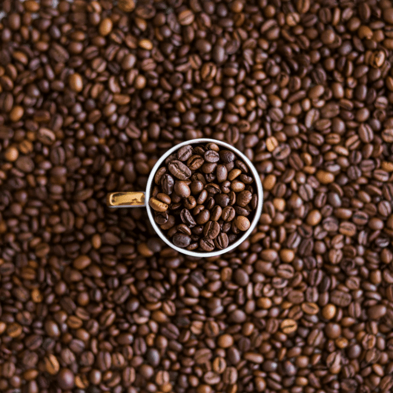 golden coffee cup filled with whole coffee beans