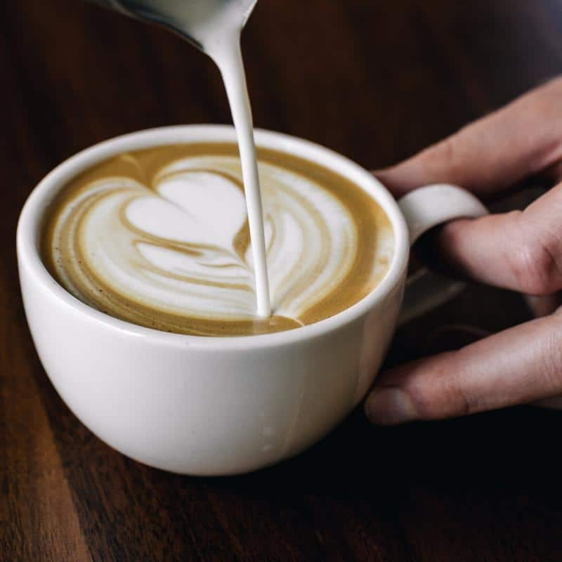a hot, milky latte being poured