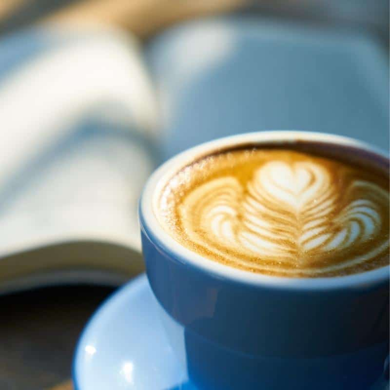 a delicious latte with a good book blurred out in the sunny background