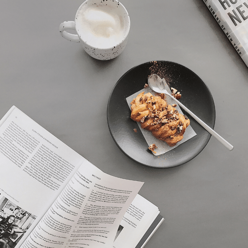 latte with walnut pastry and a book. A delicious afternoon snack.