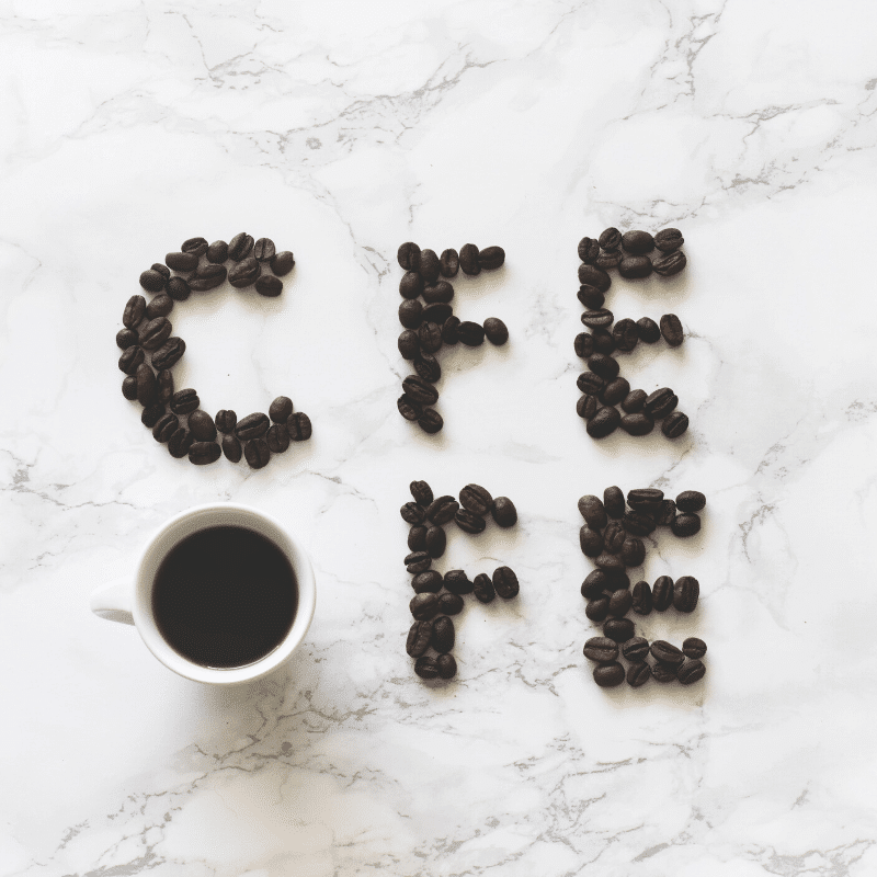 whole black coffee beans shaped into the word coffee with a black coffee cup