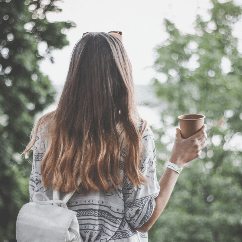 young lady holding coffee cup on her travels